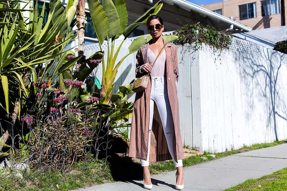 Eine enge Hose macht den Look mit Trench lässig und modern gleichermaßen